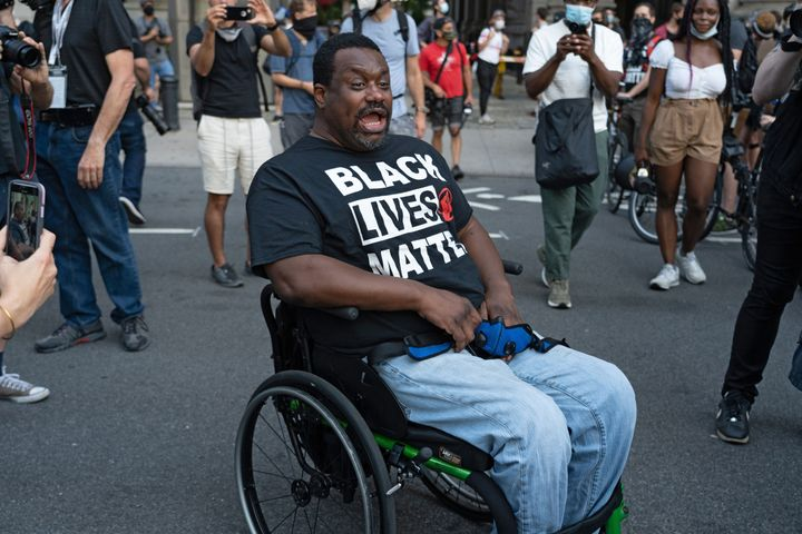 A Black Lives Matter protester in a wheelchair leads others in chanting during a rally outside New York City Hall in July.