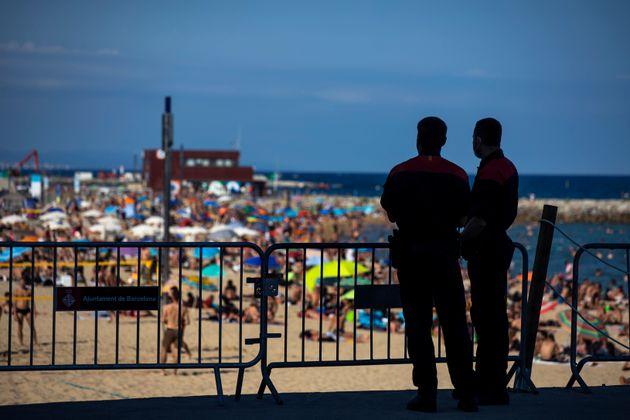 Dos agentes controlan el aforo en una playa llena de bañistas en