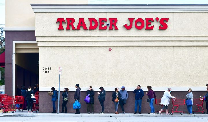 A woman wearing a facemask pushes her cart to the back of the line as people line up before the opening of a Trader Joe's sto