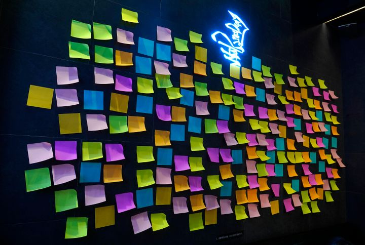 """A Hong Kong Cafe, known as a """"yellow shop"""" because its owners expressed sympathy for protesters, has a wall decorated with blank post-it notes in Hong Kong on July 9, 2020. Stores that supported the protest movement by putting up protest artwork and sticky notes filled with words of encouragement from customers have since taken them down, out of fear that its contents could land them in trouble with the authorities. Instead, they have put up blank sticky notes as a way to show solidarity with the movement."""