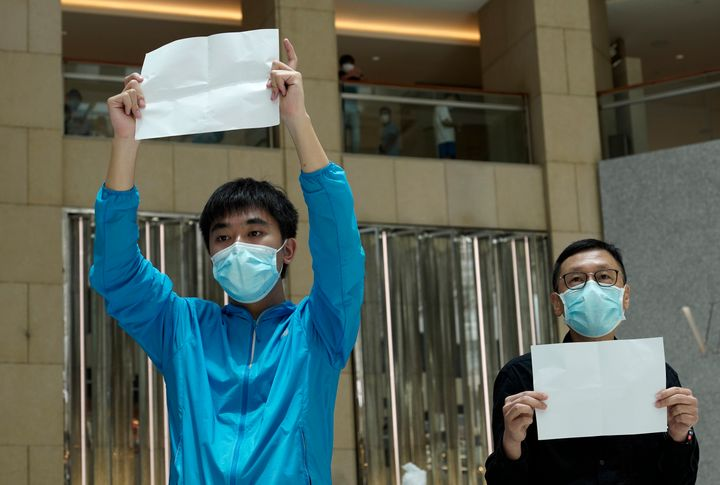 Protesters raise white papers as they gather at a shopping mall in Central during a pro-democracy protest against Beijing's national security law in Hong Kong on Tuesday. A few of protesters were detained and released shortly afterward.