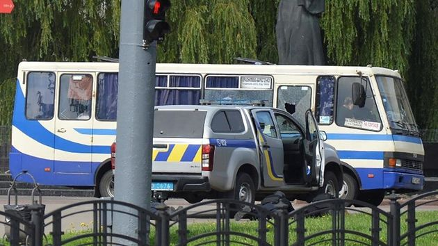 El autobús secuestrado, con las cortinas bajadas y un cristal roto por el impacto de algún