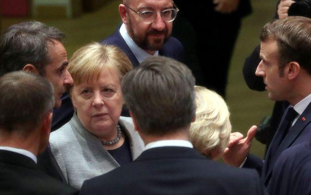 German Chancellor Angela Merkel, third left, speaks with Greek Prime Minister Kyriakos Mitsotakis, left,...