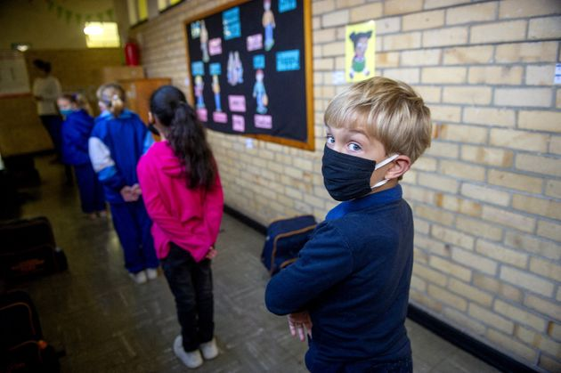 Grade 1 students line up for class in Cape Town on July 6 as schools reopen in South Africa. Sixty-two...