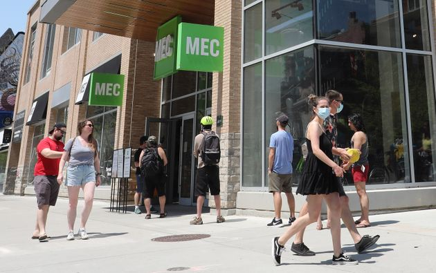 People line up to enter the Mountain Equipment Co-op (MEC) store at Queen and John streets in Toronto,...