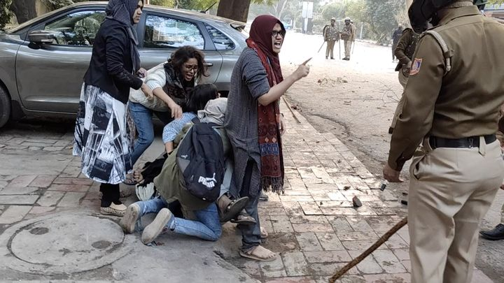 Women form a human shield around a man beaten by police during protests against new citizenship law, at Jamia Millia Islamia University in New Delhi, December 15, 2019 in this screen grab obtained from a social media video.
