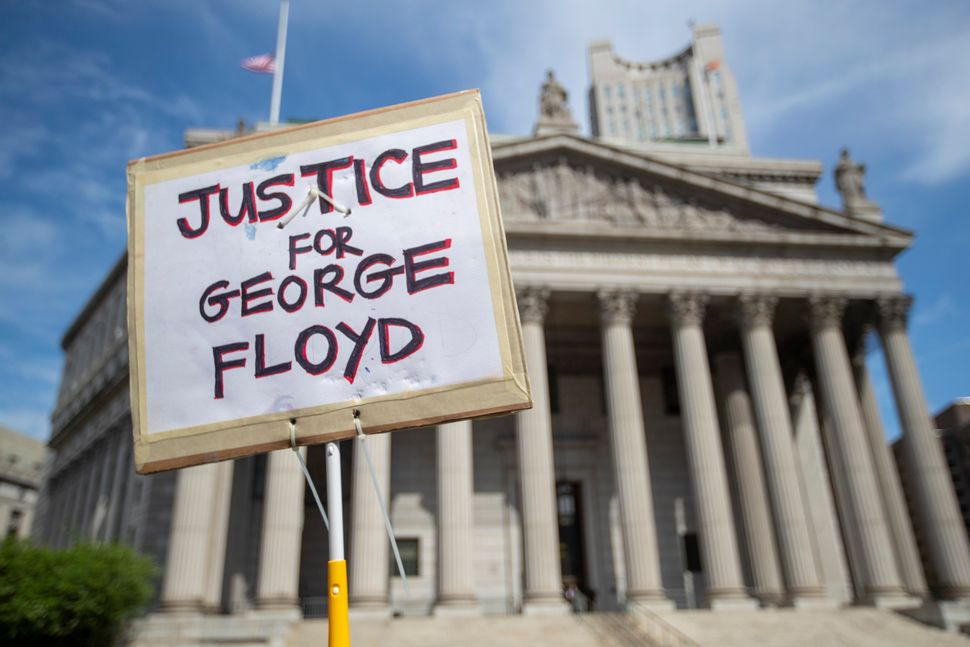 A protester holds a sign in front of New York Supreme Court on May 29 demanding justice for George Floyd, a handcuffed black