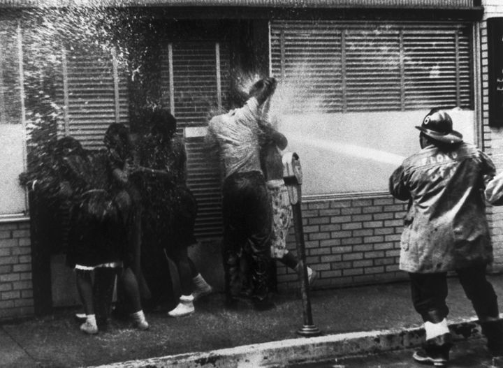A firefighter sprays people with a high-pressure hose as they protest segregation in Birmingham, Alabama, in May 1963.