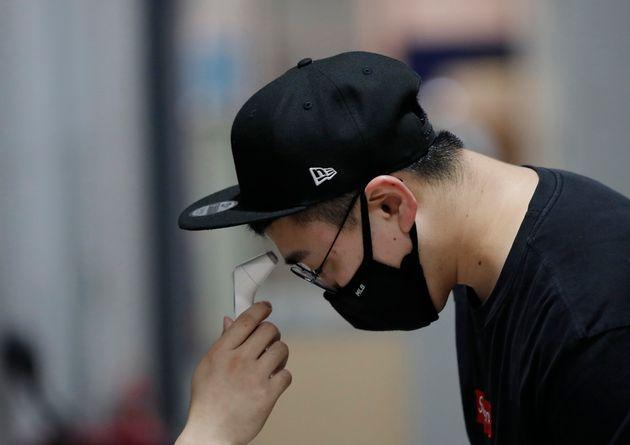 21일 서울의 모 건물에서 한 남성이 코로나19 확산 예방을 위한 열 체크를 진행하고