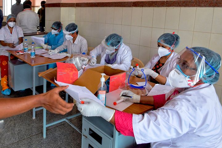 Medical professionals issue modules to members of the media before getting tested for Covid-19 at the C.V. Raman Government Hospital in Bangalore on April 25, 2020.