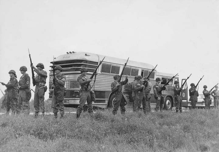 Members of the U.S. military guard a bus carrying civil rights activists known as Freedom Riders while they travel into Jacks