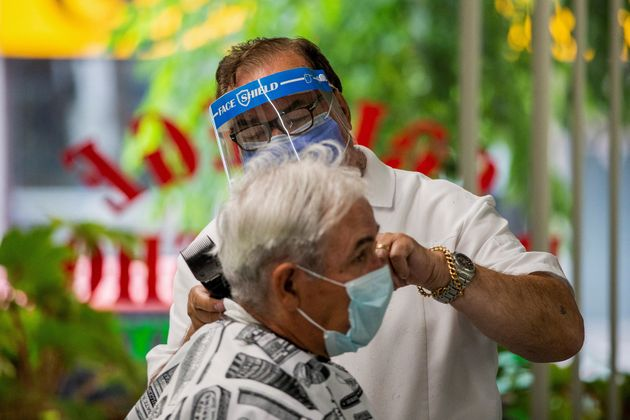 Joaquim Correia of College Barber Shop cuts a customer's hair as the provincial phase 2 of reopening...