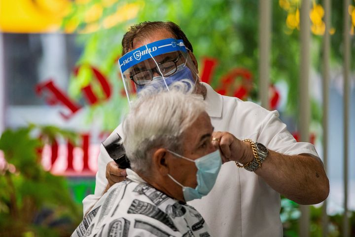 Joaquim Correia of College Barber Shop cuts a customer's hair as the provincial phase 2 of reopening from the coronavirus disease (COVID-19) restrictions begins in Toronto and June 24, 2020.