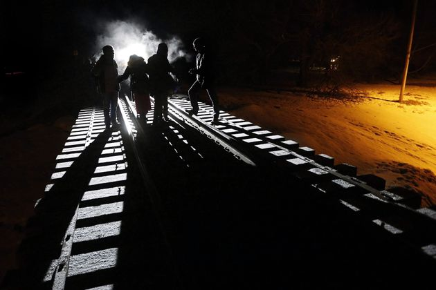Migrants from Somalia cross into Canada illegally from the United States by walking down a train track...