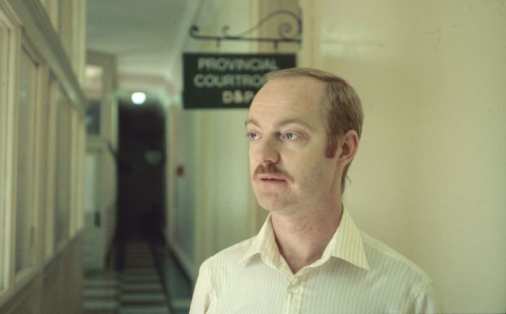 Dennis Findlay standing in the hallway outside a courtroom at Queen Street Court House, where legal proceedings following the 1981 bathhouse raids took place.