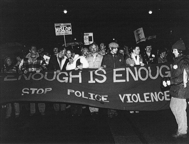 "Following the bathhouse raids, protestors march from Queen's Park to Toronto Police division 52, carrying a banner that reads ""Enough is Enough."""