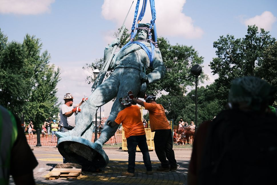 Workers in Richmond prepare to load a monument to Confederate soldiers and sailors onto a flatbed truck on July 8, 2020.