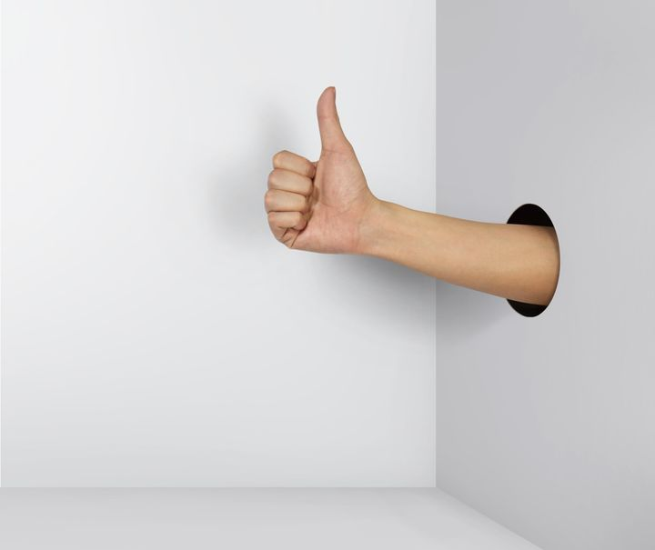 A hand gives a thumb's up out of a hole in the wall.