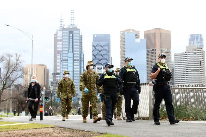 Police and the Australian military patrol the banks of the Yarra River on July 23, 2020 in Melbourne, Australia. Face masks or face coverings are now mandatory for anyone leaving their homes in the Melbourne metropolitan area or the Mitchell Shire.