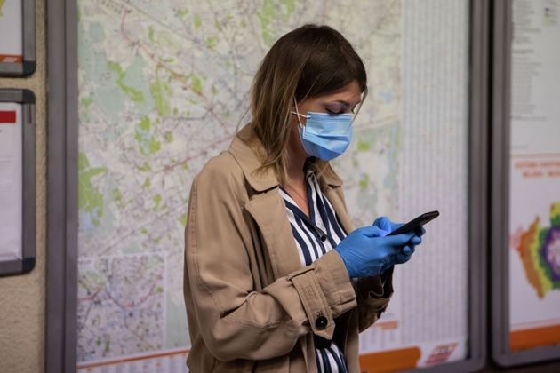 A woman uses a mobile phone while waiting for a train in Milan, Italy, on May 4,