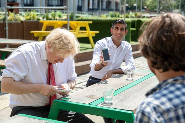British Prime Minister Boris Johnson and Chancellor Rishi Sunak use their phones during a visit to a...