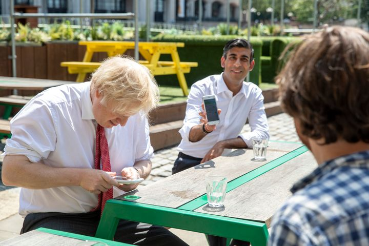 British Prime Minister Boris Johnson and Chancellor Rishi Sunak use their phones during a visit to a restaurant in London, Ju