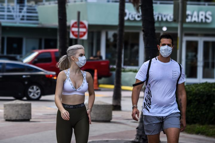 Tourists wearing masks walk near the closed Miami Beach on March 19.