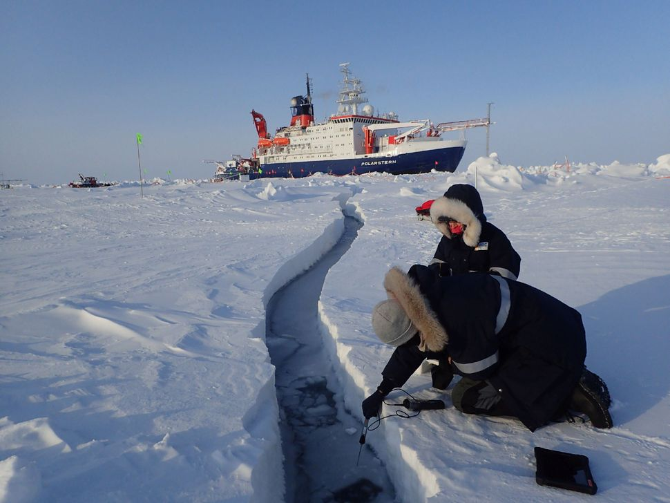 Researchers sample water for lead, with Polarstern in the background.