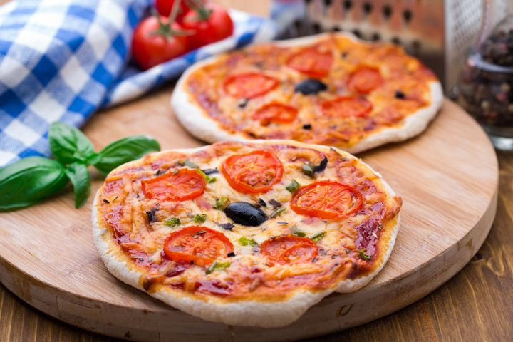 Vegetarian mini pizza with cherry tomatoes, paprika and olives