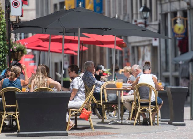 People sit at an outdoor terrace in Montreal on Wednesday as the COVID-19 pandemic continues in Canada...