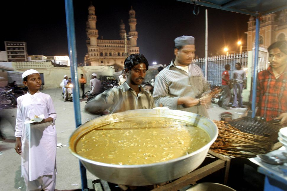 HYDERABAD, INDIA: An Indian vendor prepares kebabs and non-vegetarian delicacies in his stall outside the Mecca mosque with the Char Minar in the background in Hyderabad, 20 October 2005. I