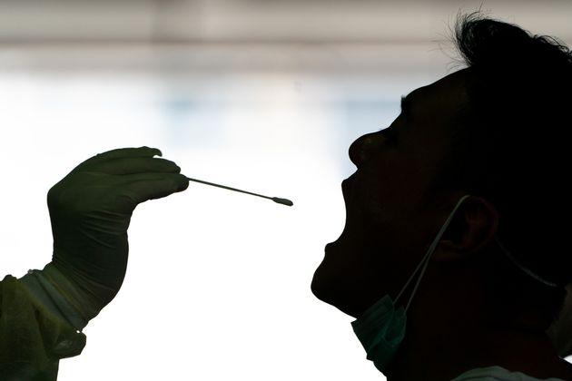 Toman muestras a un paciente en Hong Kong para realizarle una prueba de PCR de