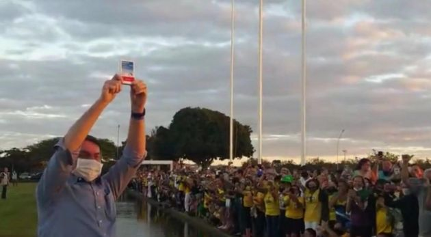 Bolsonaro saúda uma caixa de cloroquina em frente a seus