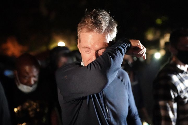 Portland Mayor Ted Wheeler reacts after being exposed to tear gas fired by federal officers while attending a protest against