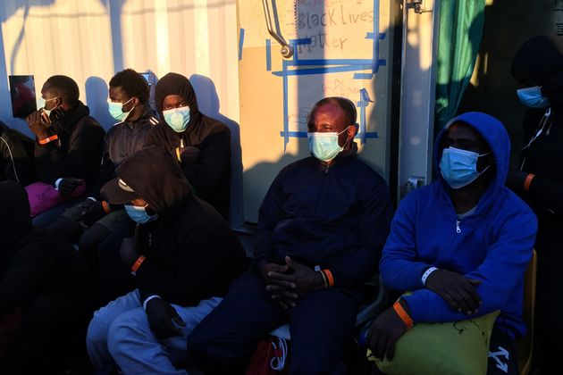 Migrants wearing protective facemasks on board of the humanitarian aid boat Ocean Viking, chartered by...