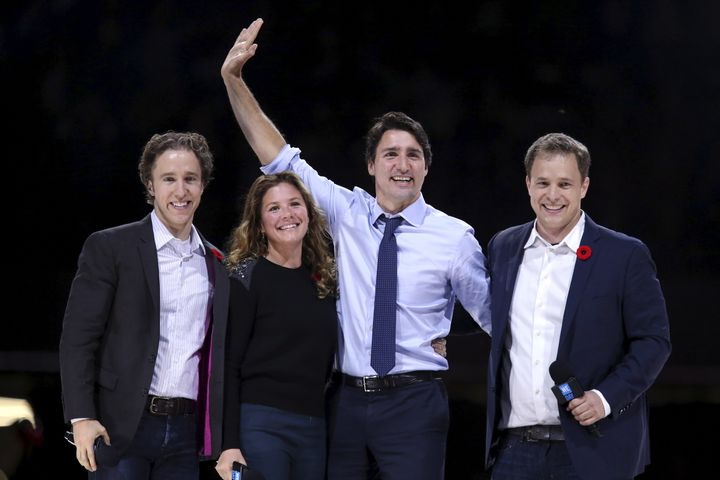 Prime Minister Justin Trudeau waves while on stage with his wife Sophie and WE Day co-founders Craig Kielburger (left) and Marc Kielburger (right) during a WE Day event in Ottawa on Nov. 10, 2015.