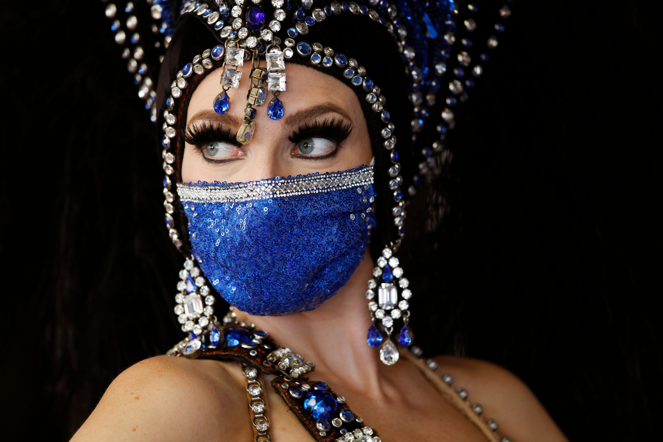 A show performer in a face mask stands by the door at the reopening of Bally's Las Vegas hotel and casino, Thursday, July 23,