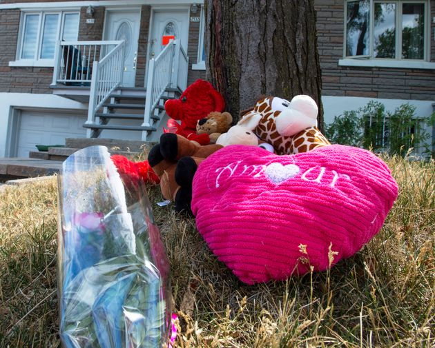 Flowers and toys are left in front of a home where a six-year-old girl was stabbed to death in