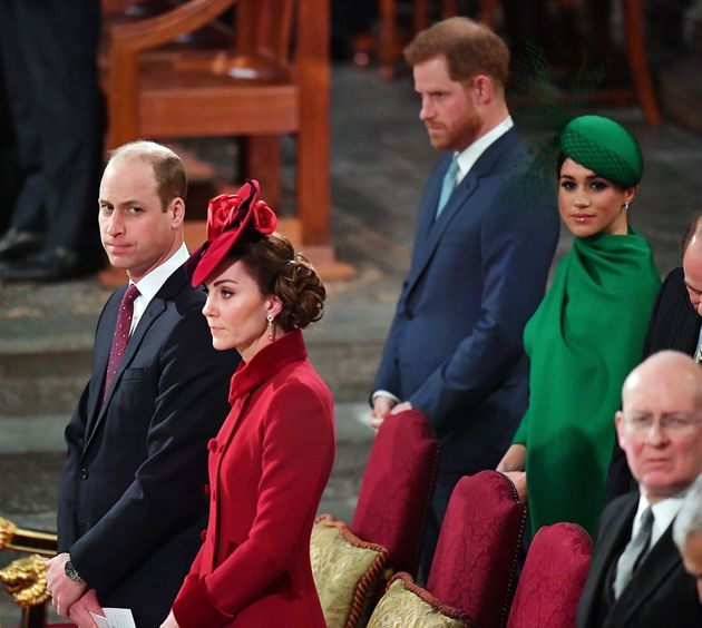 Britain's Prince Harry, Duke of Sussex, (2nd R) and Britain's Meghan, Duchess of Sussex (R) sit behind...
