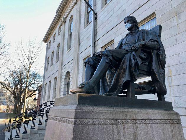 La statue de l'université de John Harvard arborant un masque de