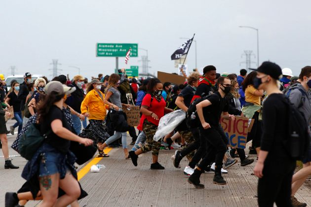 People run for cover moments after a driver in a blue Jeep rammed through the crowd of protesters and...