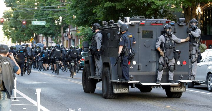 Seattle Police ride on a vehicle behind bicycle police during a Black Lives Matter protest march, Saturday, July 25, 2020, in