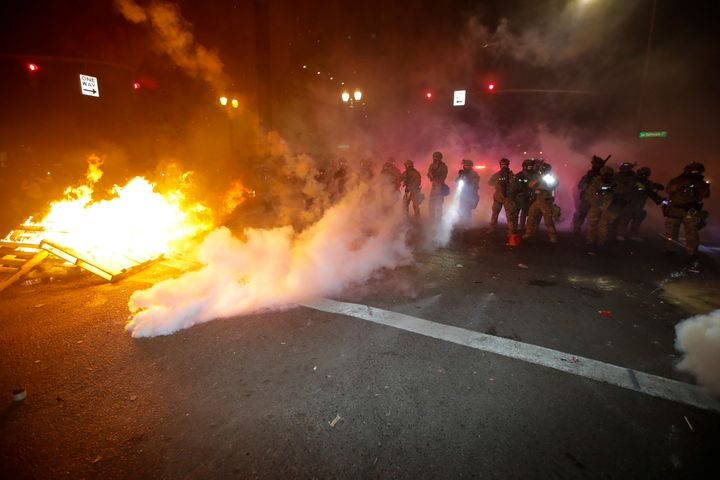 Federal officers clear a street where demonstrator had set a fire during a Black Lives Matter protest at the Mark O. Hatfield