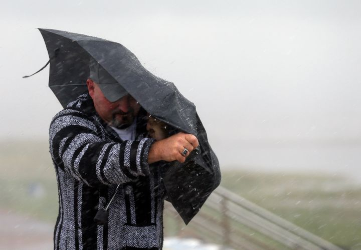 A man holds the front on his umbrella as he fights heavy rain and wind on Seawall Boulevard, Saturday, July 25, 2020, in Galv