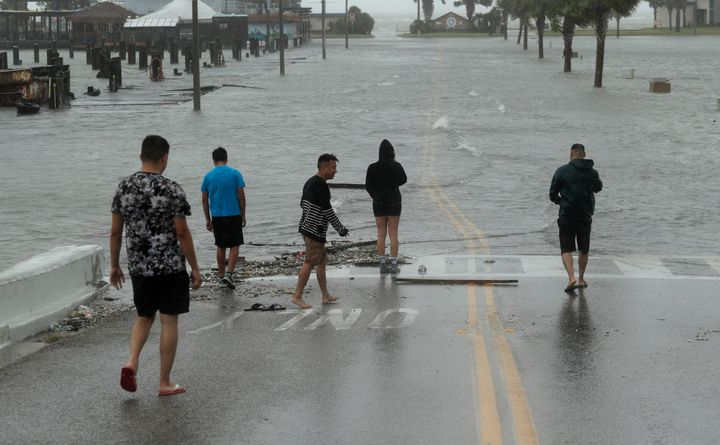 Onlookers gather on a road beginning to flood as Hurricane Hanna makes landfall, Saturday, July 25, 2020, in Corpus Christi,