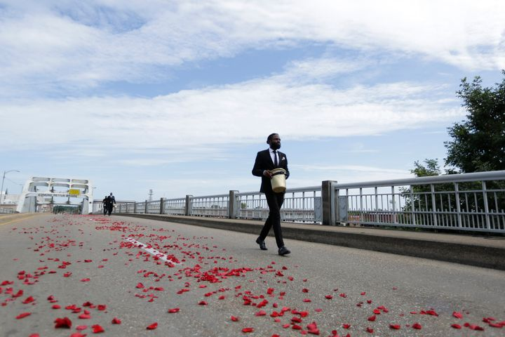 A man places flower petals on the Edmund Pettus Bridge ahead of Rep. John Lewis' casket crossing during a memorial service fo
