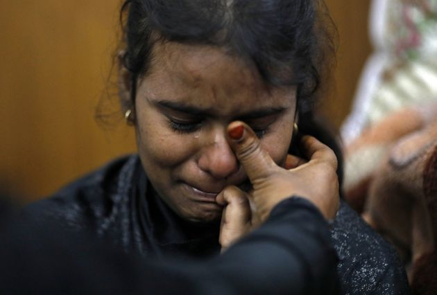 A Muslim girl is consoled in a shelter camp after she and her family fled their home during the Delhi...