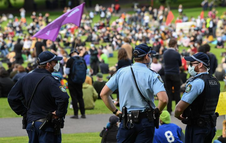 SYDNEY, AUSTRALIA - JULY 05: Police wearing face masks watch people gather at a rally against Black Deaths in Custody in The Domain on July 05, 2020 in Sydney, Australia.