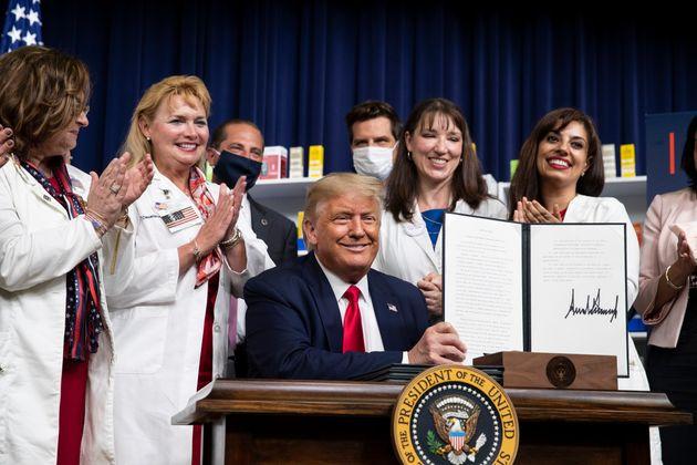 도널드 트럼프 대통령이 백악관에서 약값 인하 행정명령에 서명한 뒤 기념촬영을 하고 있다. 2020년