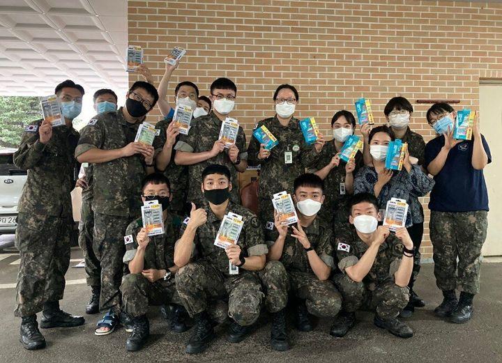 장형정 소령이 기부한 질레트 면도기 및 면도젤 세트를 들고 있는 국군포천병원의 장병들의 모습.